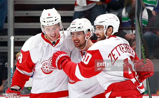 Justin Abdelkader and Henrik Zetterberg congratulate Tomas Tatar of the Detroit Red Wings who scored against the Vancouver Canucks during their NHL...