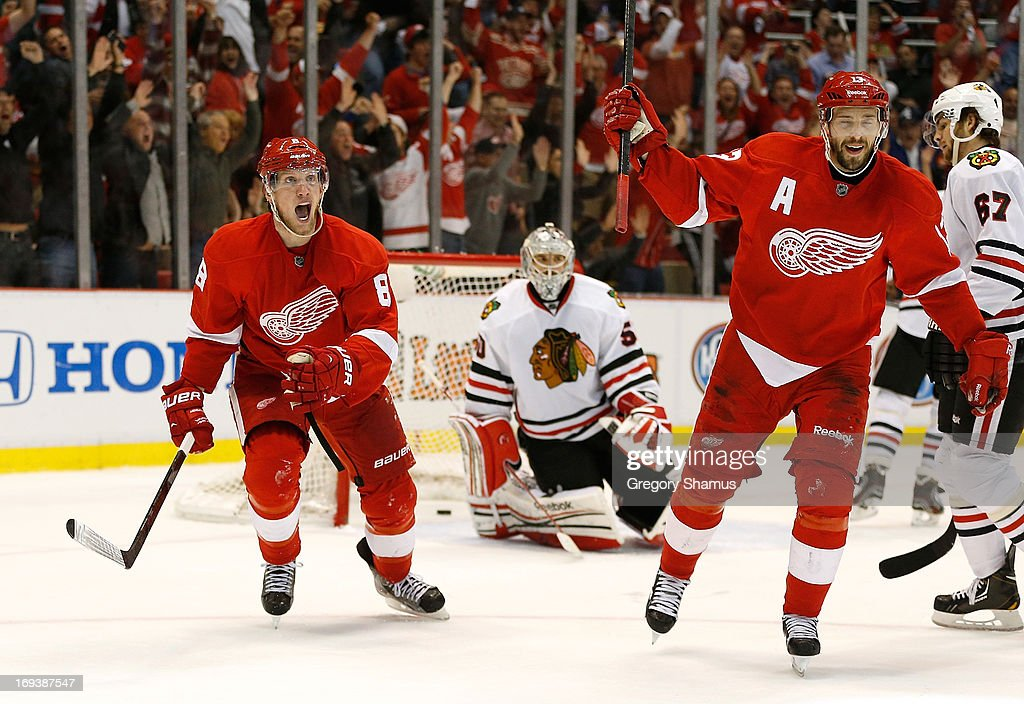 Justin Abdelkader #8 and Pavel Datsyuk #13 of the Detroit Red Wings celebrate a second period goal by teammate Jakub Kindl #4 in front of Corey Crawford #50 of the Chicago Blackhawks in Game Four of the Western Conference Semifinals during the 2013 NHL Stanley Cup Playoffs at Joe Louis Arena on May 23, 2013 in Detroit, Michigan.