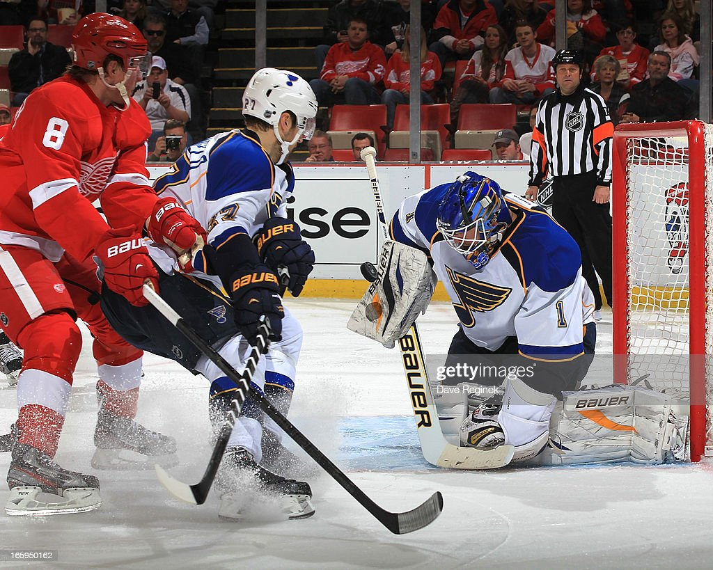 Justin Abdelkader #8 of the Detroit Red Wings and Alex Pietrangelo #27 of the St. Louis Blues crash the net as goalie Brian Elliot #1 makes a blocker save during a NHL game at Joe Louis Arena on April 7, 2013 in Detroit, Michigan.