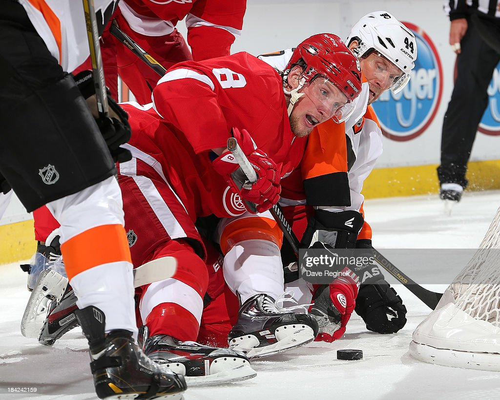<a gi-track='captionPersonalityLinkClicked' href=/galleries/search?phrase=Justin+Abdelkader&family=editorial&specificpeople=2271858 ng-click='$event.stopPropagation()'>Justin Abdelkader</a> #8 of the Detroit Red Wings and <a gi-track='captionPersonalityLinkClicked' href=/galleries/search?phrase=Kimmo+Timonen&family=editorial&specificpeople=201521 ng-click='$event.stopPropagation()'>Kimmo Timonen</a> #44 of the Philadelphia Flyers fight for the puck along the ice during a NHL game at Joe Louis Arena on October 12, 2013 in Detroit, Michigan.