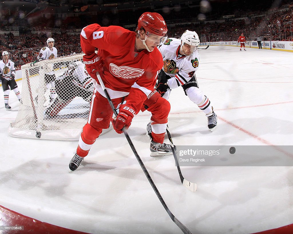 Justin Abdelkader #8 of the Detroit Red Wings and Niklas Hjalmarsson #4 of the Chicago Blackhawks battle for the puck behind the net during a NHL game at Joe Louis Arena on March 31, 2013 in Detroit, Michigan. Chicago defeated Detroit 7-1