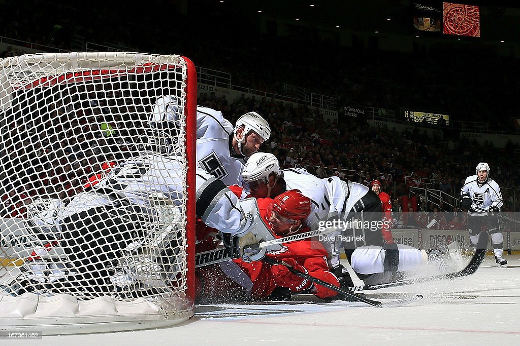 Justin Abdelkader #8 of the Detroit Red Wings, Anze Kopitar #11 and Robyn Regehr #44 of the Los Angeles Kings all slide into goalie Jonathan Quick #32 during a NHL game at Joe Louis Arena on April 24, 2013 in Detroit, Michigan.