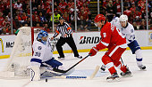 Justin Abdelkader of the Detroit Red Wings battles for puck control as Victor Hedman of the Tampa Bay Lightning and Ben Bishop defend during the...