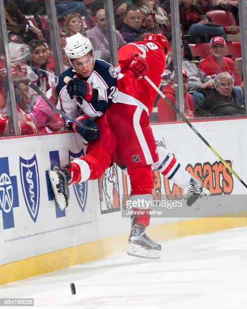Justin Abdelkader of the Detroit Red Wings checks Ryan Murray of the Columbus Blue Jackets into the boards during an NHL game at Joe Louis Arena on...