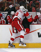 Justin Abdelkader of the Detroit Red Wings dumps Brandon Saad of the Chicago Blackhawks over the boards in Game Two of the Western Conference...