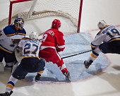 Justin Abdelkader of the Detroit Red Wings fights thru the checks of Alex Pietrangelo and Jay Bouwmeester of the St Louis Blues to score the OT...