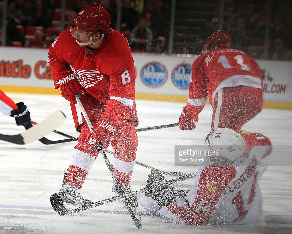 <a gi-track='captionPersonalityLinkClicked' href=/galleries/search?phrase=Justin+Abdelkader&family=editorial&specificpeople=2271858 ng-click='$event.stopPropagation()'>Justin Abdelkader</a> #8 of the Detroit Red Wings finishes his check on <a gi-track='captionPersonalityLinkClicked' href=/galleries/search?phrase=Tomas+Fleischmann&family=editorial&specificpeople=554398 ng-click='$event.stopPropagation()'>Tomas Fleischmann</a> #14 of the Florida Panthers during an NHL game at Joe Louis Arena on December 7, 2013 in Detroit, Michigan.