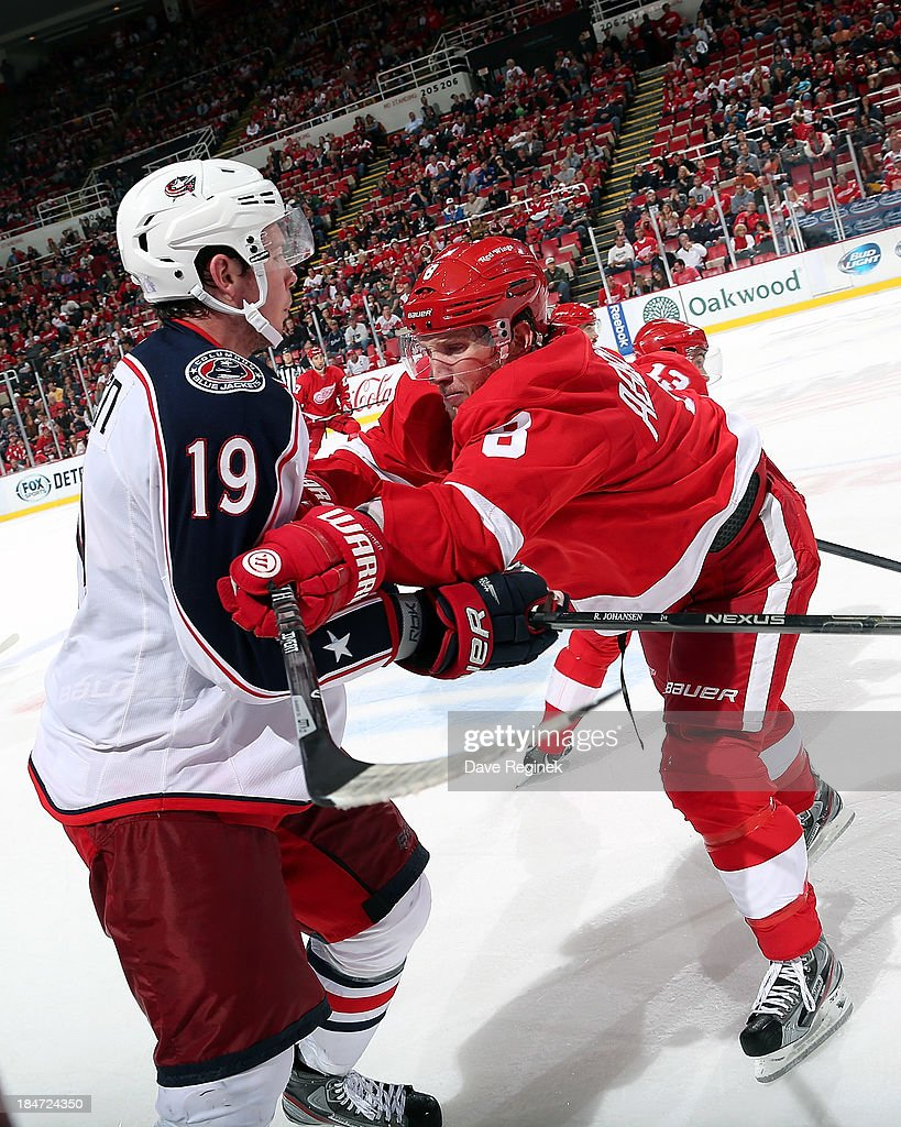 <a gi-track='captionPersonalityLinkClicked' href=/galleries/search?phrase=Justin+Abdelkader&family=editorial&specificpeople=2271858 ng-click='$event.stopPropagation()'>Justin Abdelkader</a> #8 of the Detroit Red Wings finishes his check on <a gi-track='captionPersonalityLinkClicked' href=/galleries/search?phrase=Ryan+Johansen&family=editorial&specificpeople=6698841 ng-click='$event.stopPropagation()'>Ryan Johansen</a> #19 of the Columbus Blue Jackets during a NHL game at Joe Louis Arena on October 15, 2013 in Detroit, Michigan. Detroit defeated Columbus 2-1.