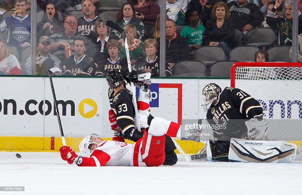 Justin Abdelkader #8 of the Detroit Red Wings is knocked to the ice by Alex Goligoski #33 of the Dallas Stars at the American Airlines Center on April 27, 2013 in Dallas, Texas.