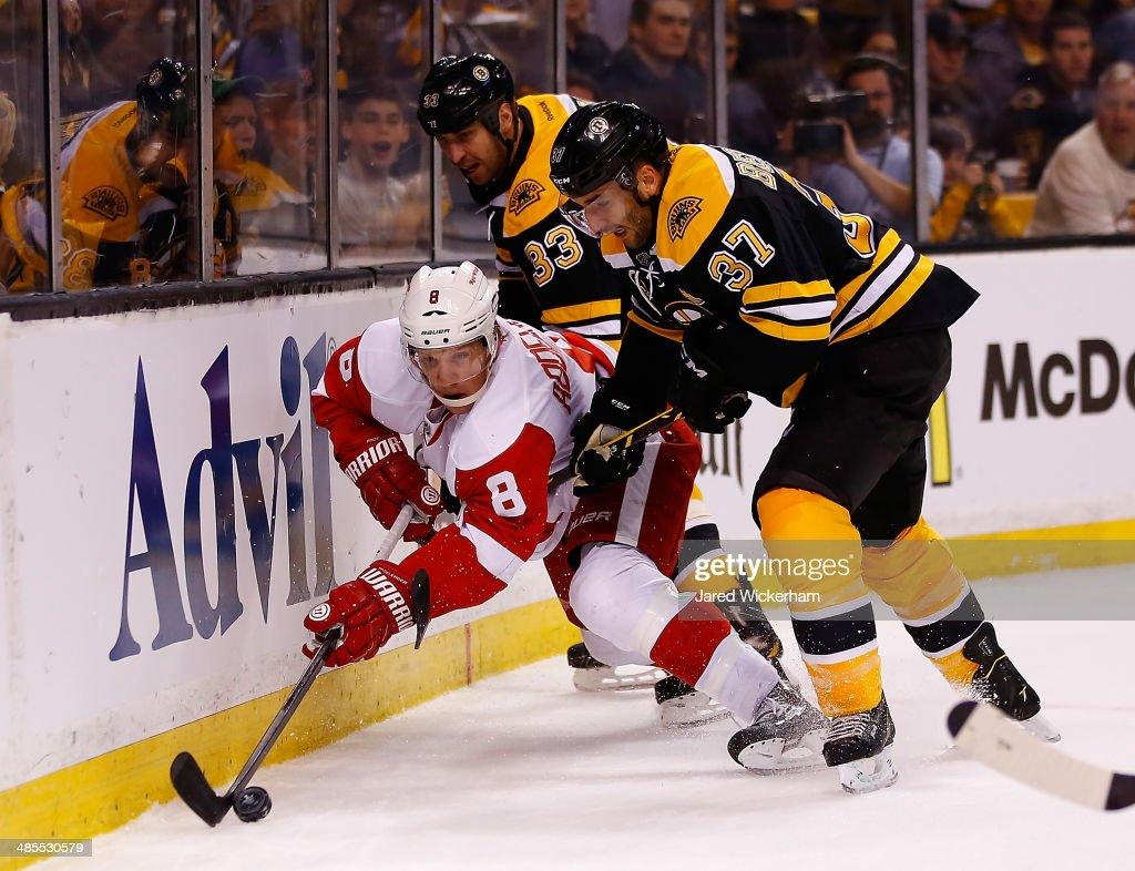 Justin Abdelkader #8 of the Detroit Red Wings reaches for the puck underneath Patrice Bergeron #37 and Zdeno Chara #33 of the Boston Bruins in the first period in Game One of the First Round of the 2014 NHL Stanley Cup Playoffs at TD Garden on April 18, 2014 in Boston, Massachusetts.