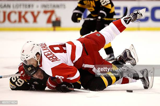 Justin Abdelkader of the Detroit Red Wings takes down Tim Schaller of the Boston Bruins during the first period at Joe Louis Arena on January 18 2017...