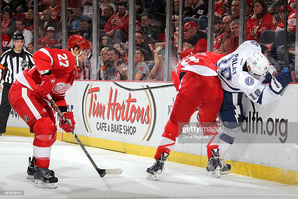 <a gi-track='captionPersonalityLinkClicked' href=/galleries/search?phrase=Justin+Abdelkader&family=editorial&specificpeople=2271858 ng-click='$event.stopPropagation()'>Justin Abdelkader</a> #8 of the Detroit Red Wings takes the body on Ondrej Palat #18 of the Tampa Bay Lightning as teammate <a gi-track='captionPersonalityLinkClicked' href=/galleries/search?phrase=Kyle+Quincey&family=editorial&specificpeople=2234340 ng-click='$event.stopPropagation()'>Kyle Quincey</a> #27 pick up the loose puck during an NHL game on March 30, 2014 at Joe Louis Arena in Detroit, Michigan. Detroit defeated Tampa Bay 3-2