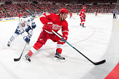 Justin Abdelkader of the Detroit Red Wings turns with the puck in front of Tyler Bozak of the Toronto Maple Leafs during an NHL game at Joe Louis...