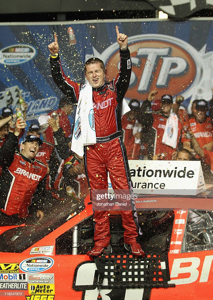 Justin Allgaier driver of the Brandt Chevrolet celebrates winning the NASCAR Nationwide Series STP 300 at Chicagoland Speedway on June 4 2011 in...