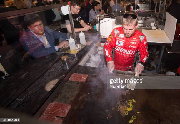 Justin Allgaier driver of the BRANDT Chevrolet cooks a cheesesteak at Reading Terminal Market during the 2nd Annual XFINITY Takeover on May 9 2017 in...