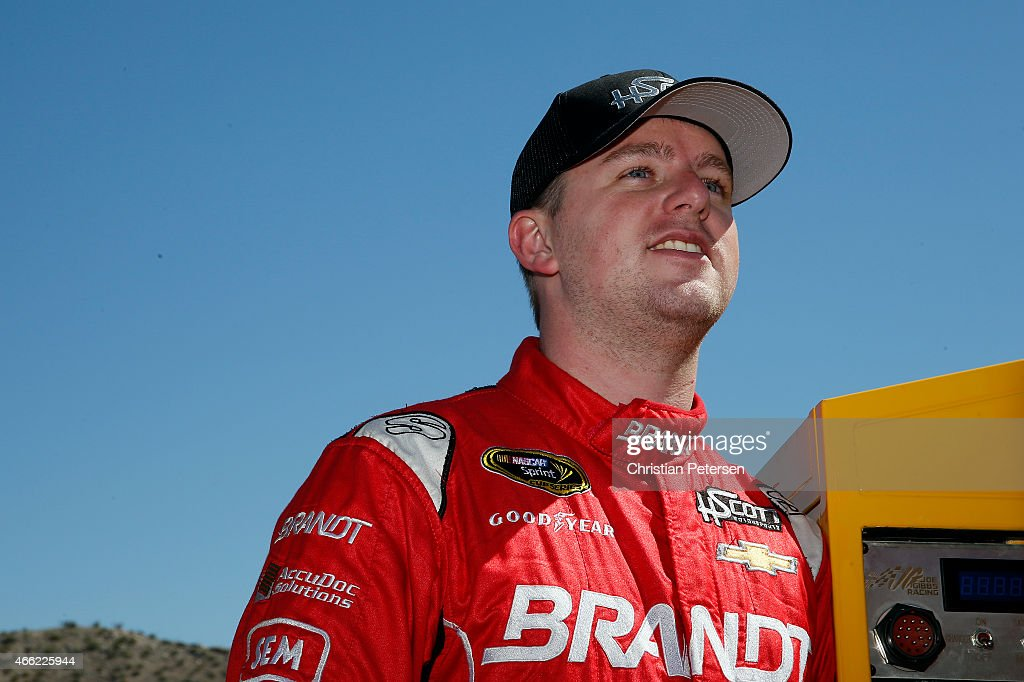 Justin Allgaier driver of the BRANDT Chevrolet stands in the garage area during practice for the NASCAR Sprint Cup Series CampingWorldcom 500 at...