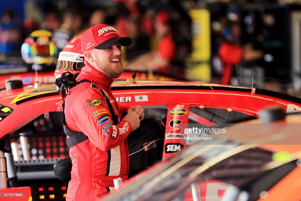 Justin Allgaier driver of the BRANDT Chevrolet stands in the garage area during practice for the NASCAR XFINITY Series PowerShares QQQ 300 at Daytona...