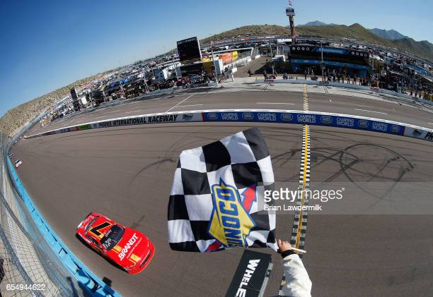 Justin Allgaier driver of the BRANDT Chevrolet takes the checkered flag to win the NASCAR XFINITY Series DC Solar 200 at Phoenix International...