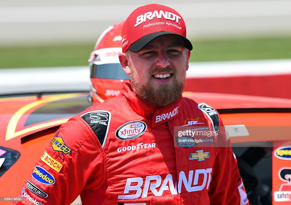 Justin Allgaier driver of the BRANDT Chevrolet walks on the grid during the NASCAR XFINITY Series Menards 250 at Michigan International Speedway on...