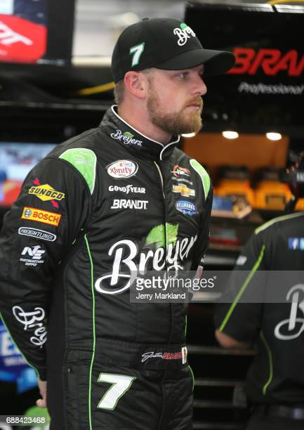 Justin Allgaier driver of the Breyers Chevrolet stands in the garage during practice for the NASCAR Xfinity Series Hisense 4K TV 300 at Charlotte...