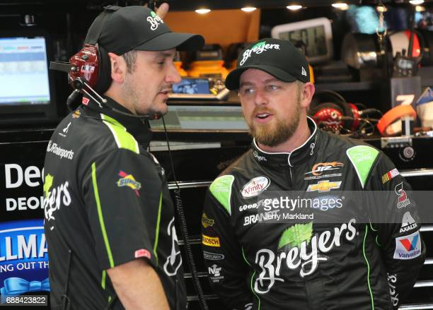 Justin Allgaier driver of the Breyers Chevrolet talks to a crew member during practice for the NASCAR Xfinity Series Hisense 4K TV 300 at Charlotte...