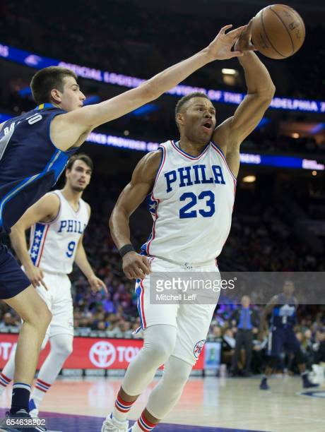 Justin Anderson of the Philadelphia 76ers reaches for the ball along with Nicolas Brussino of the Dallas Mavericks in the fourth quarter at the Wells...