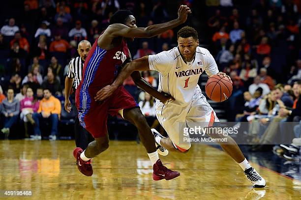 Justin Anderson of the Virginia Cavaliers drives against against Greg Mortimer of the South Carolina State Bulldogs during the first half of a game...