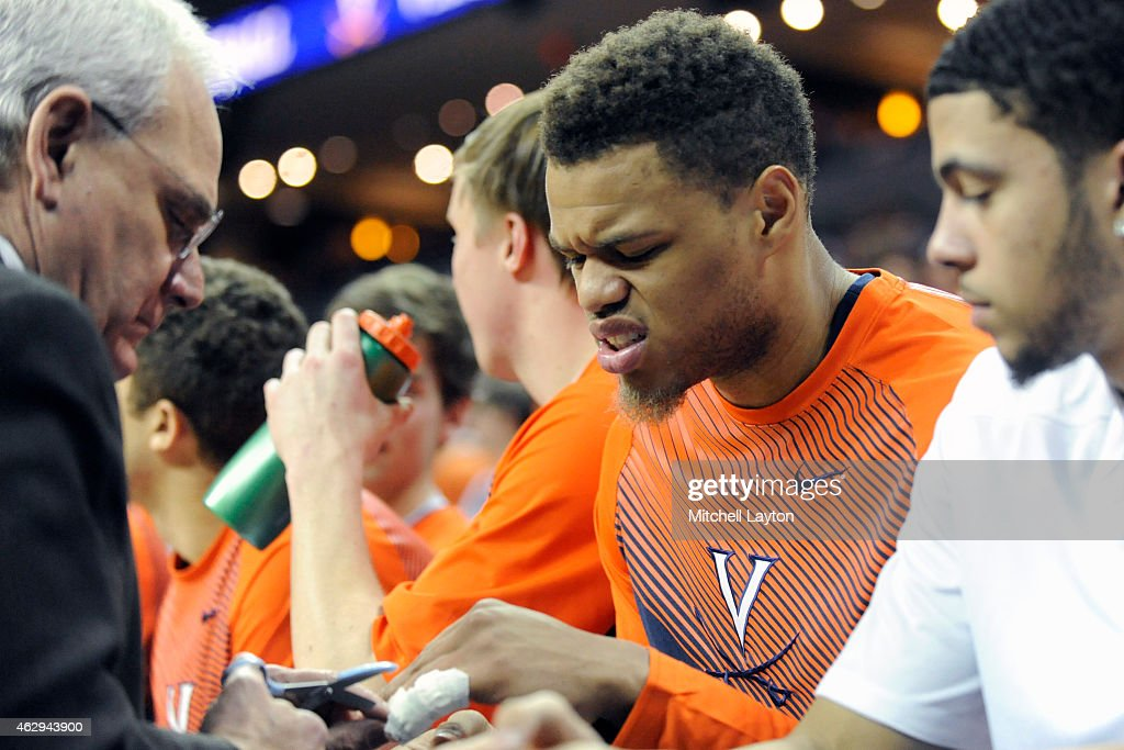Justin Anderson #1 of the Virginia Cavaliers has his finger worked on during a college basketball game against the Louisville Cardinals at the John Paul Jones Arena on February 7, 2015 in Charlottesville, Virginia. The Cavaliers won 52-47.