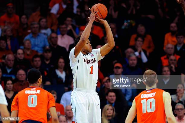 Justin Anderson of the Virginia Cavaliers takes a shot between Michael Gbinije and Trevor Cooney of the Syracuse Orange during the second half at...