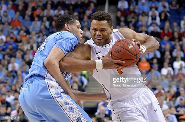 Justin Anderson of the Virginia Cavaliers tries to drive past Justin Jackson of the North Carolina Tar Heels during the semifinals of the 2015 ACC...