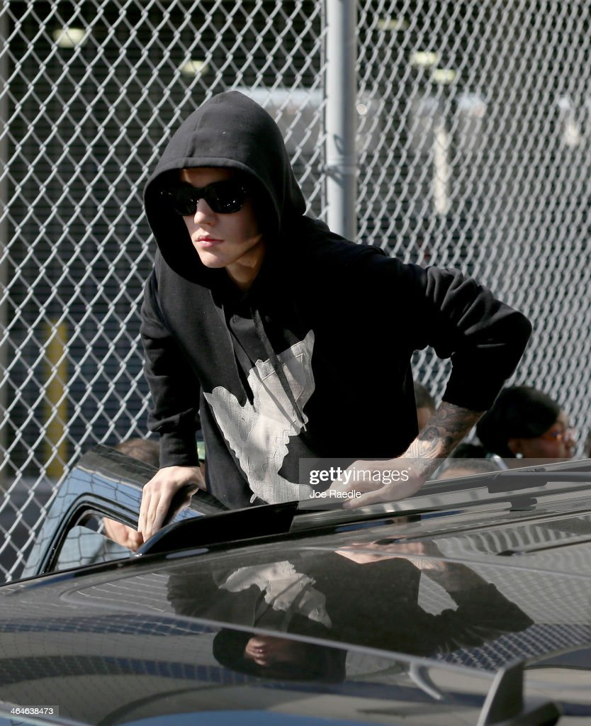 Justin Bieber prepares to stand on his vehicle after exiting from the Turner Guilford Knight Correctional Center on January 23, 2014 in Miami, Florida. Justin Bieber was charged with drunken driving, resisting arrest and driving without a valid license after Miami Beach police found the pop star street racing Thursday morning.