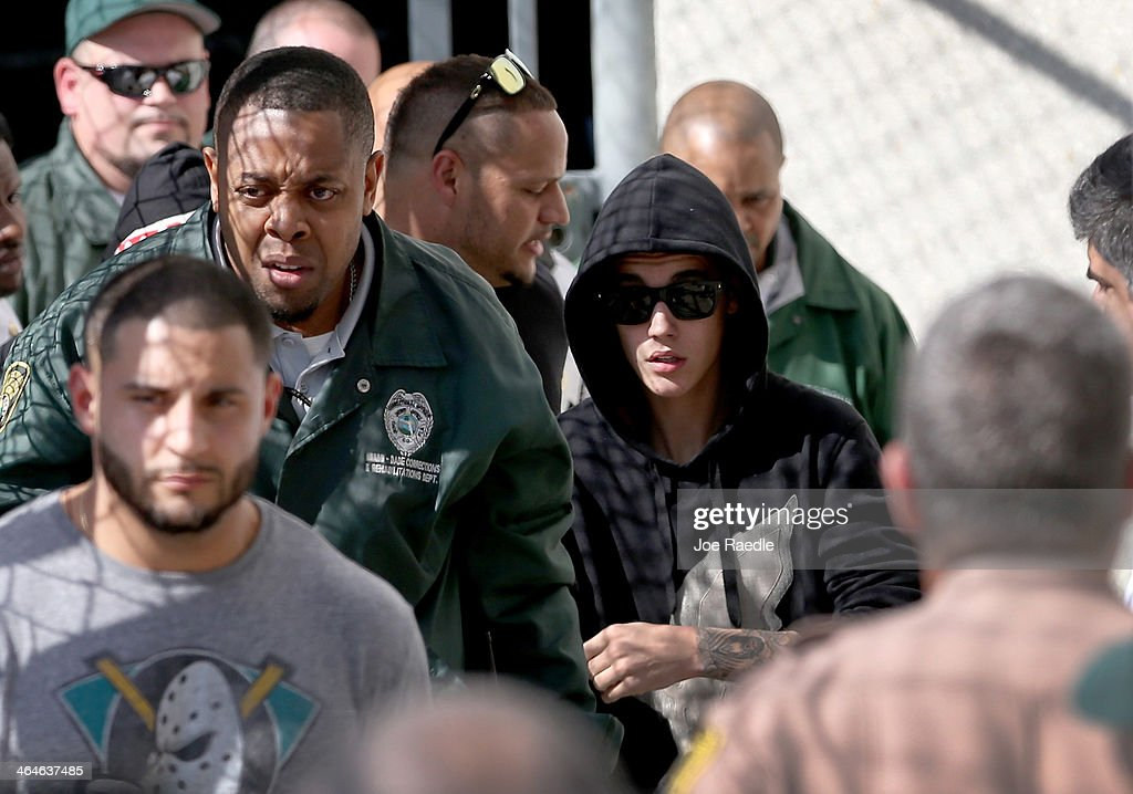 Justin Bieber (R), with bodyguard Michael Arana (Left Foreground), exits from the Turner Guilford Knight Correctional Center on January 23, 2014 in Miami, Florida. Justin Bieber was charged with drunken driving, resisting arrest and driving without a valid license after Miami Beach police found the pop star street racing Thursday morning.
