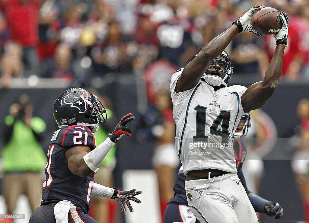 <a gi-track='captionPersonalityLinkClicked' href=/galleries/search?phrase=Justin+Blackmon&family=editorial&specificpeople=6236641 ng-click='$event.stopPropagation()'>Justin Blackmon</a> #14 of the Jacksonville Jaguars makes a catch over Brice McCain #21 of the Houston Texans at Reliant Stadium on November 18, 2012 in Houston, Texas. Houston wins 43-37 in overtime.