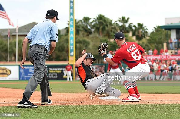 Justin Bohn of the Miami Marlins slides into third base under a tag by Jacob Wilson of the St Louis Cardinals during the sixth inning of a spring...