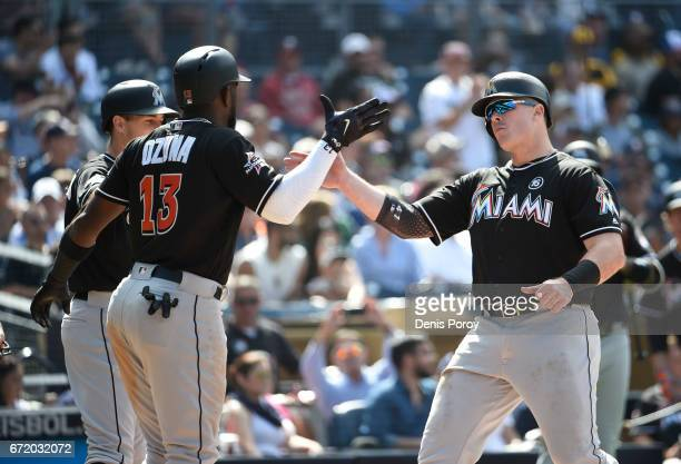 Justin Bour of the Miami Marlins is congratulated by Marcell Ozuna after hitting a threerun home run during the sixth inning of a baseball game...