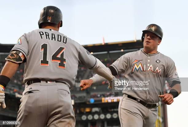 Justin Bour of the Miami Marlins is congratulated by Martin Prado after Bour hit a solo home run against the San Francisco Giants in the top of the...
