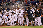 Justin Bour of the Miami Marlins is greeted by teammates at home plate after he hit a three run walkoff home run to end the game against the San...