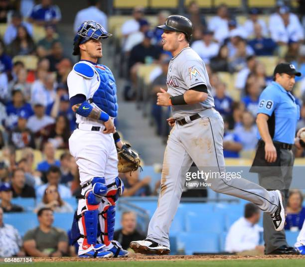 Justin Bour of the Miami Marlins scores on his solo homerun to tie the game 11 in front of Yasmani Grandal of the Los Angeles Dodgers during the...