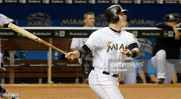 Justin Bour of the Miami Marlins watches his fifth inning home run in front of catcher Jonathan Lucroy of the Milwaukee Brewers at Marlins Park on...
