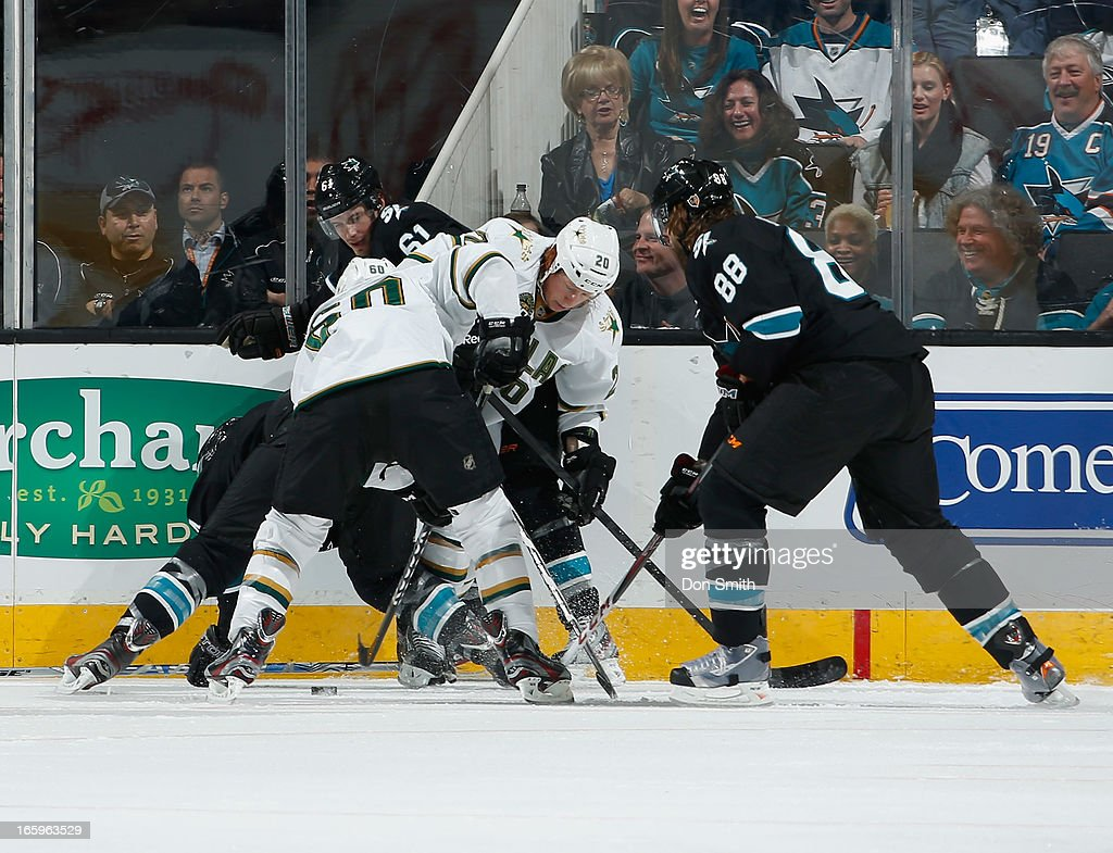 Justin Braun #61 and Brent Burns #88 of the San Jose Sharks fight for the puck against Cody Eakin #20 and Antoine Roussel #60 of the Dallas Stars during an NHL game on April 7, 2013 at HP Pavilion in San Jose, California.