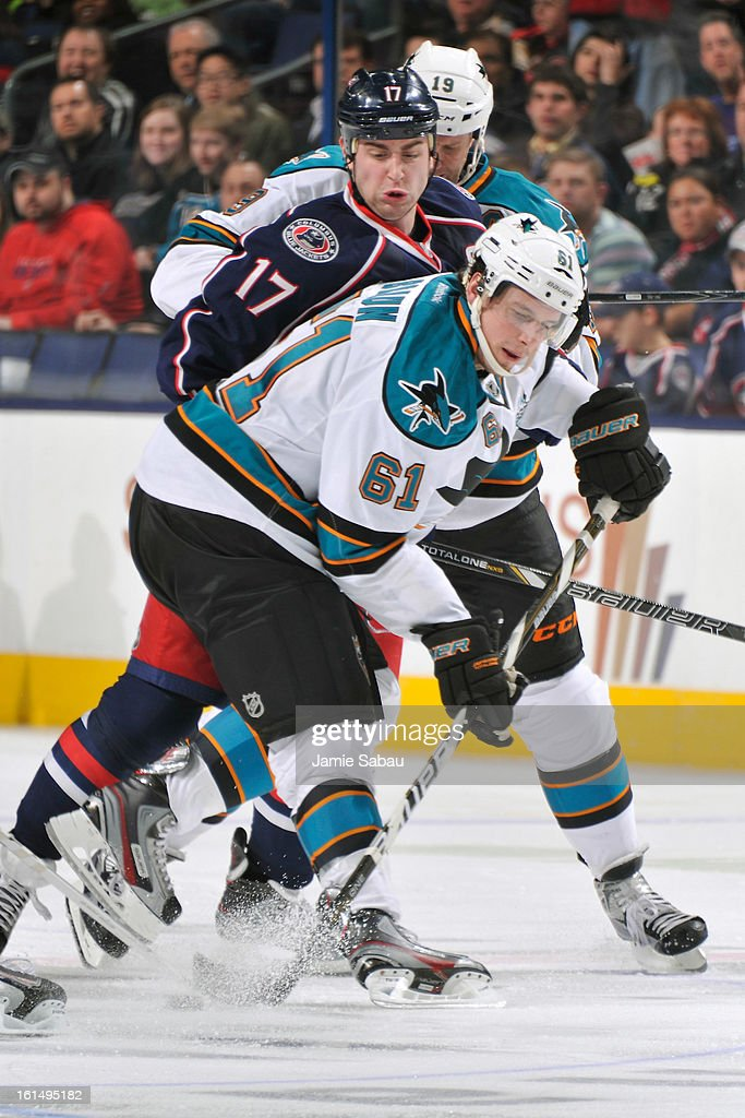 Justin Braun #61 of the San Jose Sharks and <a gi-track='captionPersonalityLinkClicked' href=/galleries/search?phrase=Brandon+Dubinsky&family=editorial&specificpeople=2271907 ng-click='$event.stopPropagation()'>Brandon Dubinsky</a> #17 of the Columbus Blue Jackets battle for control of a loose puck during the third period on February 11, 2013 at Nationwide Arena in Columbus, Ohio. Columbus defeated San Jose 6-2.