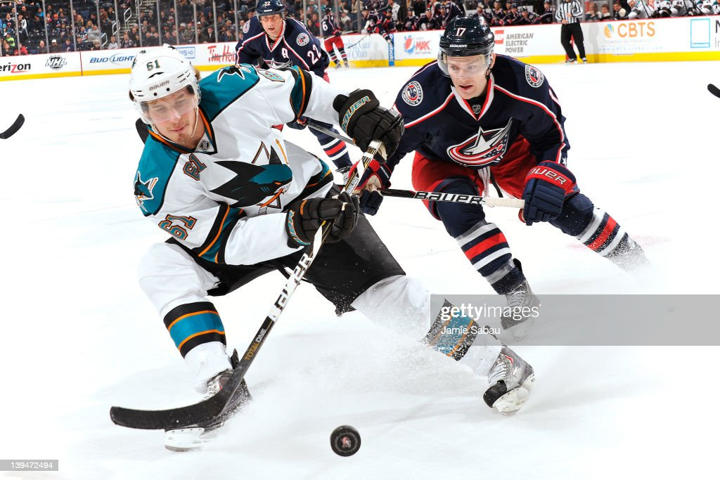 Justin Braun of the San Jose Sharks and Mark Letestu of the Columbus Blue Jackets chase after a loose puck during the third period on February 21...