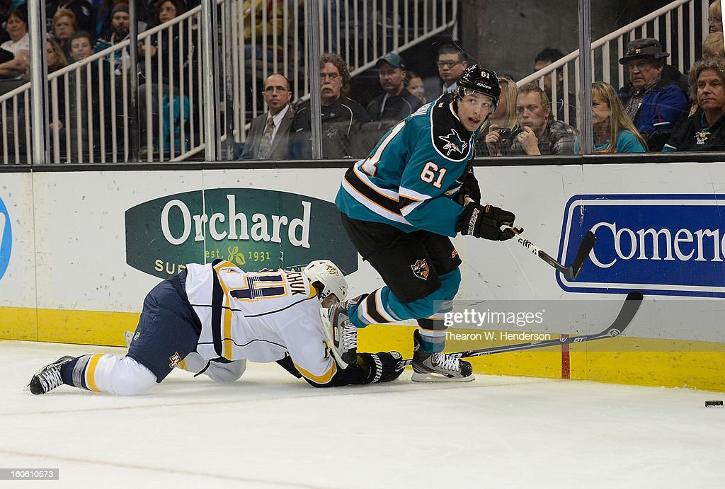 Justin Braun #61 of the San Jose Sharks skates to gain control of the puck away from Matt Halischuk #24 of the Nashville Predators at HP Pavilion on February 2, 2013 in San Jose, California.