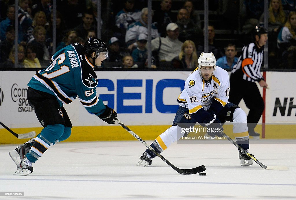 Justin Braun #61 of the San Jose Sharks skates up ice controling the puck defended by Mike Fisher #12 of the Nashville Predators in the second period of their game at HP Pavilion on February 2, 2013 in San Jose, California.
