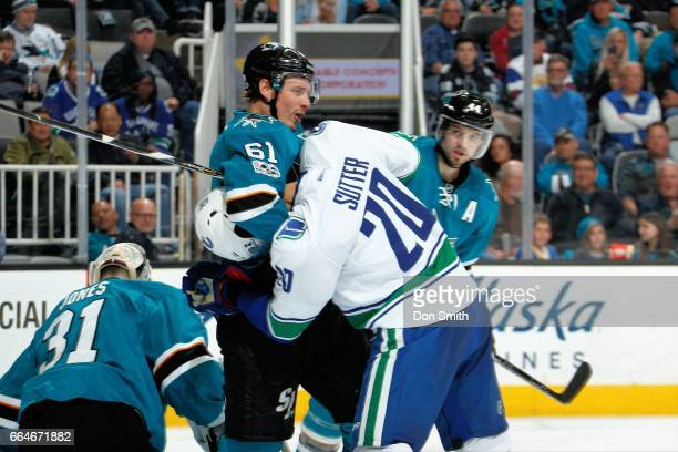 Justin Braun the San Jose Sharks and Brandon Sutter of the Vancouver Canucks get tangled up during a NHL game at SAP Center at San Jose on April 4...