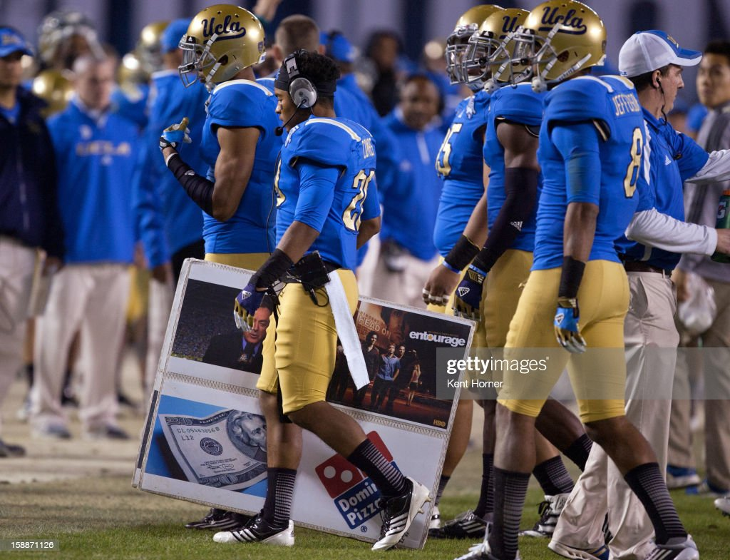 SAN DIEGO, CA - DECEMBER 27 - Justin Combs #20 of the UCLA Bruins walks back to the bench carrying a play-calling board of symbols during the second half of the game against the Baylor Bears in the Bridgepoint Education Holiday Bowl at Qualcomm Stadium on December 27, 2012 in San Diego, California.