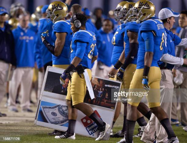 SAN DIEGO CA DECEMBER 27 Justin Combs of the UCLA Bruins walks back to the bench carrying a playcalling board of symbols during the second half of...