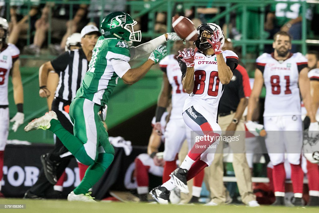 Justin Cox #31 of the Saskatchewan Roughriders breaks up a pass intended for Chris Williams #80 of the Ottawa Redblacks in the game between the Ottawa Redblacks and the Saskatchewan Roughriders at Mosaic Stadium on July 22, 2016 in Regina, Canada.