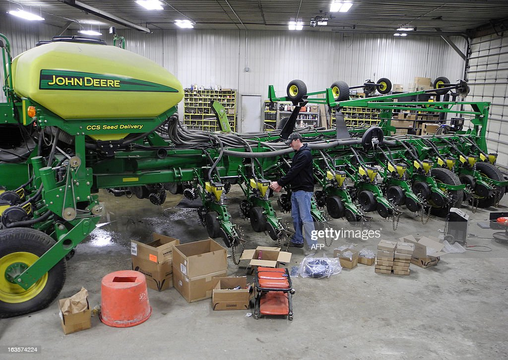 Justin Crawford prepares seeding equipment in his shed in Adair, Iowa, March 9, 2013. The machine will be used to sow corn on land he owns in the upcoming weeks. The long arms of the machine allow for faster seed distribution during the delicate seeding months. Whether farmers believe in global warming or not, US farmers from the Midwest are adapting cultrual practices and seeding habits, irrigation control and the use of machines to better tend to the land. AFP PHOTO/Juliette MICHEL