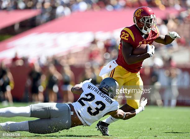 Justin Davis of the USC Trojans cuts back on Ahkello Witherspoon of the Colorado Buffaloes during the first quarter at Los Angeles Memorial Coliseum...